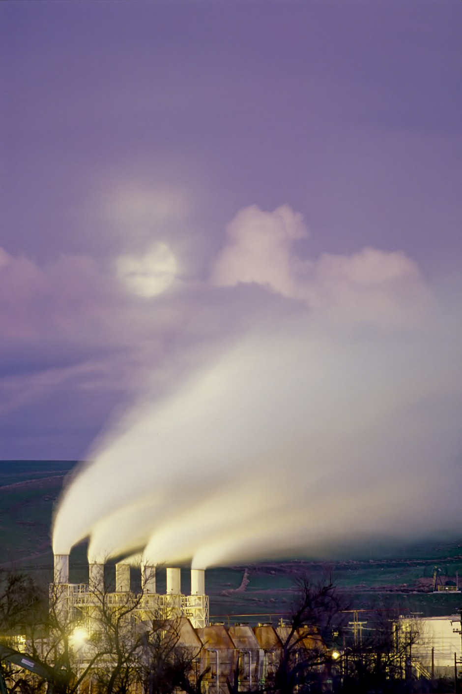 USA: California: Monterey County: Salinas Valley: Moonrise at dusk over a power plant's steaming stacks