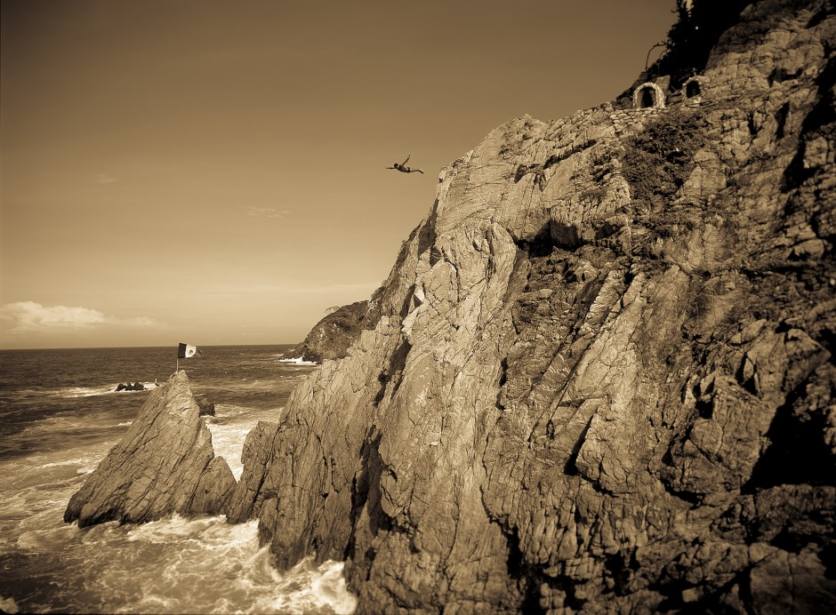 Mexico: Acapulco: A La Quebrada cliff diver leaps into the Pacific Ocean, along the Mexican Riviera