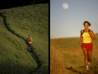 USA: California: A female runner sprinting on a trail toward the camera as the full moon rises